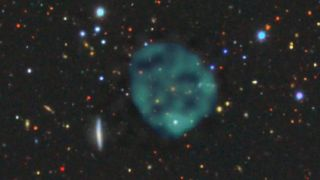 The ghostly ORC1 (blue/green fuzz), on a backdrop of the galaxies at optical wavelengths. There's an orange galaxy at the centre of the ORC, but we don't know whether it's part of the ORC, or just a chance coincidence.
