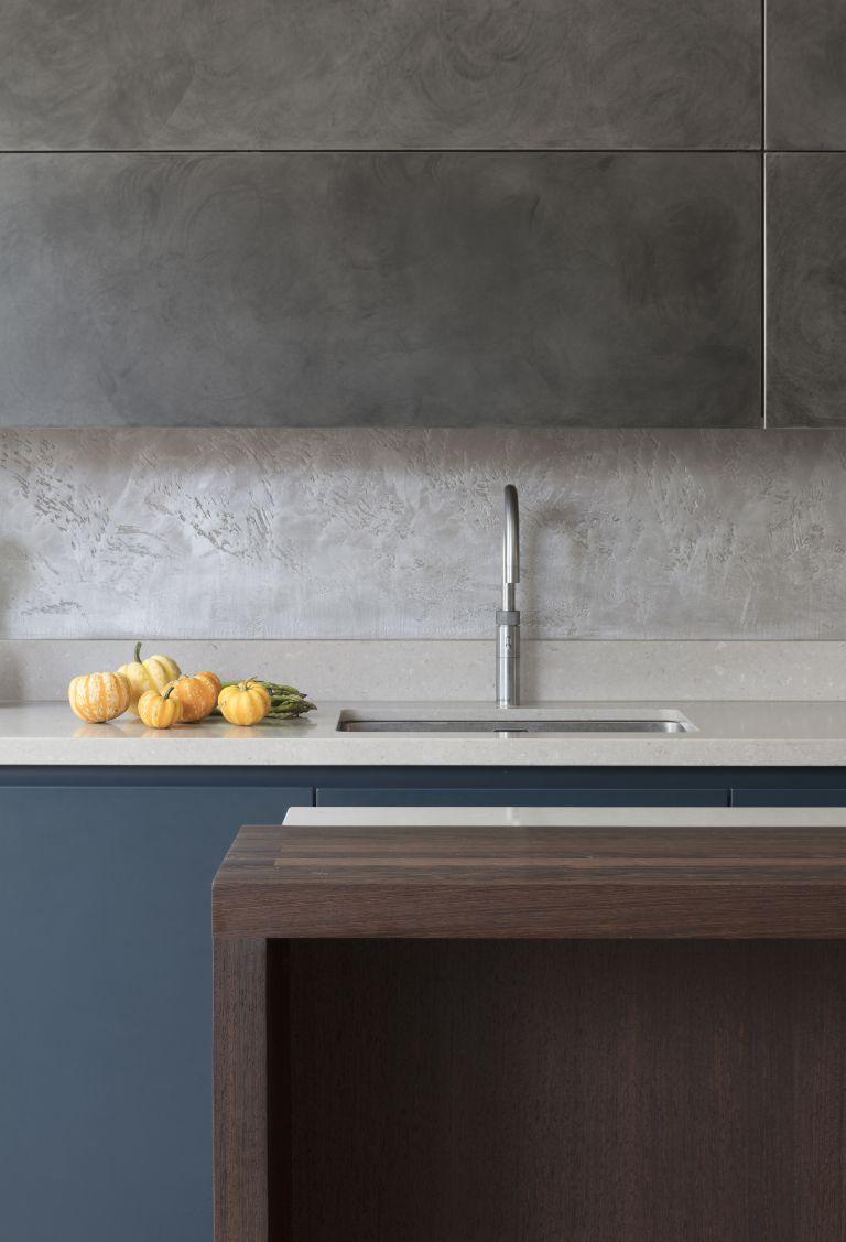 Concrete effect cabinets, backsplash, white marble countertops in a modern handlelesskitchen
