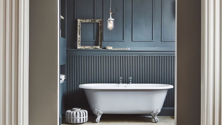 bathroom with dark blue scheme and freestanding bath and hanging light by garden trading
