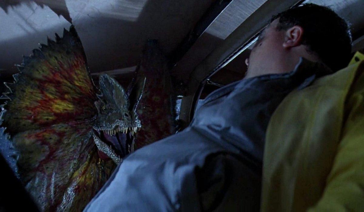 A dilophosaurus threatens Wayne Knight in Jurassic Park.