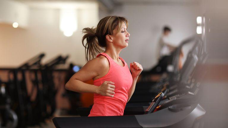 Woman running on treadmill at fitness center