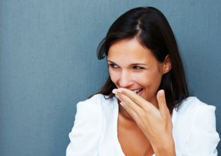 A woman giggles and covers her mouth with her hand