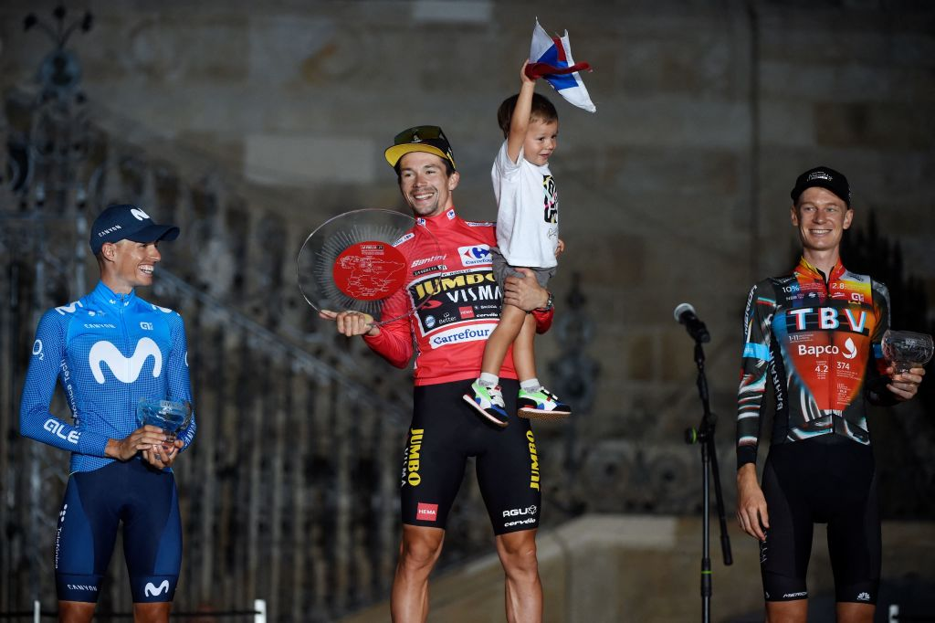 Team Jumbos Slovenian rider Primoz Roglic C holds his son Lev as celebrates winning the 2021 La Vuelta cycling tour of Spain flanked by Team Movistars Spanish rider Enric Mas L and Team Bahrains Australian rider Jack Haig after the 21st and final stage a 338 km timetrial from Padron to Santiago de Compostela on September 5 2021 Photo by MIGUEL RIOPA AFP Photo by MIGUEL RIOPAAFP via Getty Images