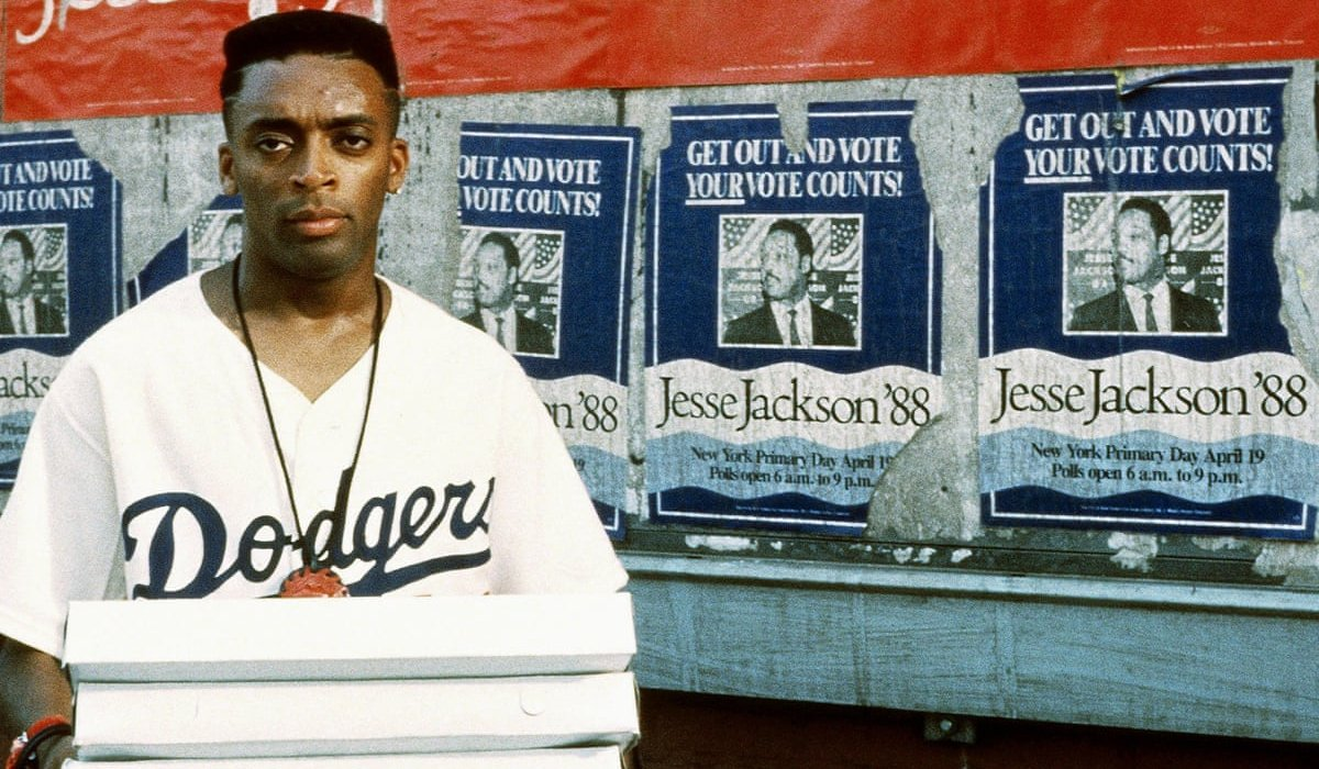 Spike Lee stands with pizzas in front of a brick wall in Do The Right Thing.