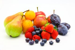Several types of fuit, including blueberries, strawberries, pears and apples, sit against a white background.