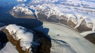 A photograph of Rink Glacier in Greenland, with a meltwater lake visible on top of the ice.