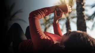 Eine Sportlerin liegt auf dem Rücken und überprüft ihre Apple Watch, die die Tidal App anzeigt