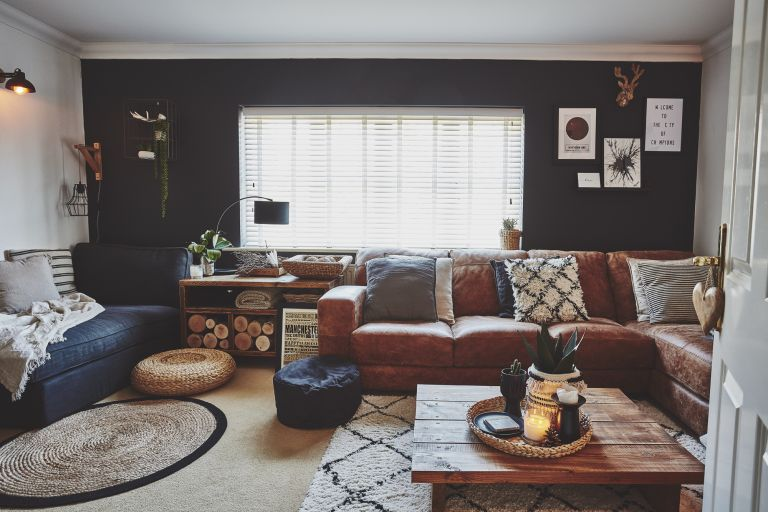 Living room with one dark black/blue wall, other white walls, tan leather L-shape sofa, black fabric sofa, rugs, rattan pouffs and coffee table made from wooden palett boards perfect for a cosy night in