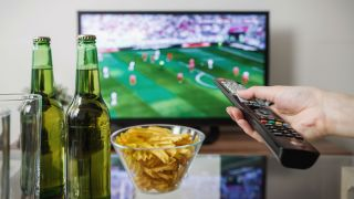 Hand using remote to watch Super Bowl on TV with beer bottles and snacks