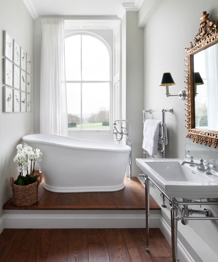 An example of how to make a small bathroom look bigger showing a small freestanding bath beneath a window on a wooden floor