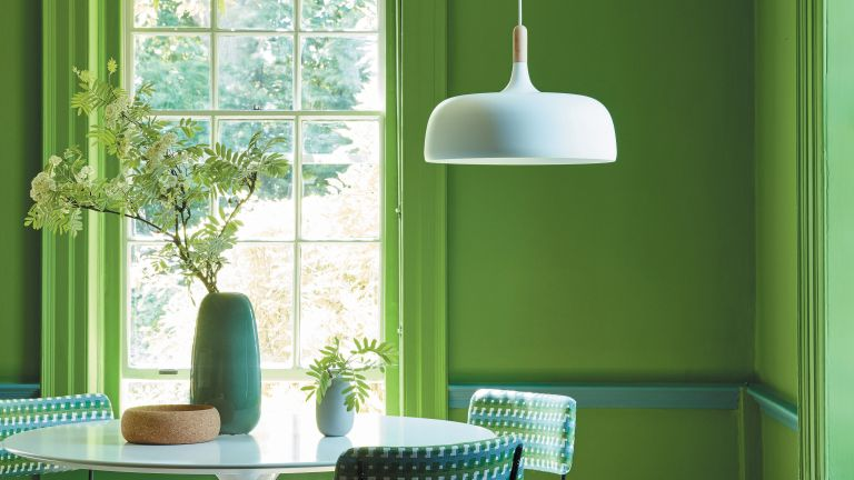 Color drenched room: Little Greene painted dining room with green paint and vase