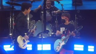 (from left): Billie Joe Armstrong, Tré Cool and 11-year-old Meyer onstage with Green Day