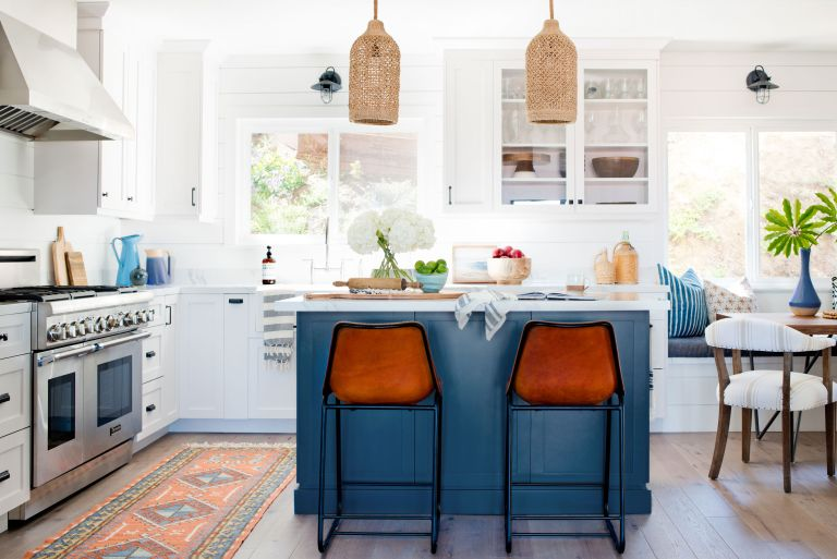 Kitchen color ideas in a white scheme with blue kitchen island, orange bar stools, rattan pendant lighting and wooden flooring.