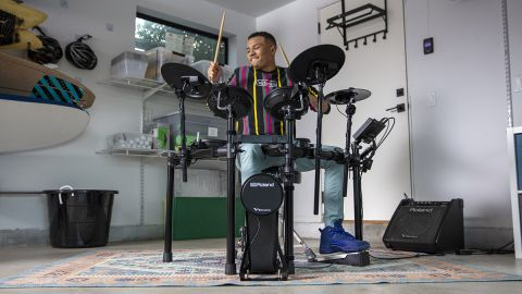 Man plays the Roland TD-07KV electronic drum set in a garage