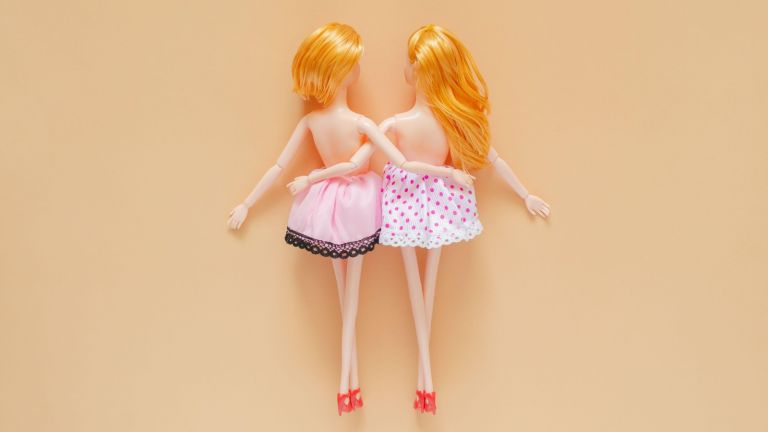 Sex doll? Two female dolls naked on top hugging each other with beige background.