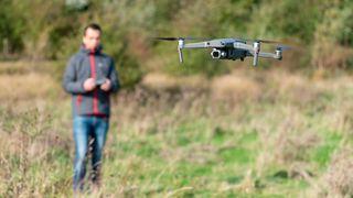 A man flying a DJI drone in a field