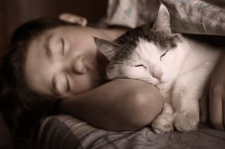 a teen boy sleeping with his cat.