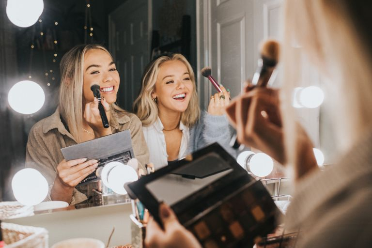 Two young woman sit in front of an illuminated mirror and apply make-up