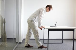 A man standing up at a desk.