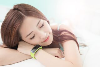 A woman snoozes while wearing a fitness tracker