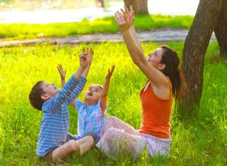 Mom, daughter and son sitting in the outdoors at a picnic meditate stretching out their hands to the sun at sunset