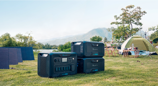 Bluetti AC300 generator and 2 B300 batteries with solar panels at a campsite.