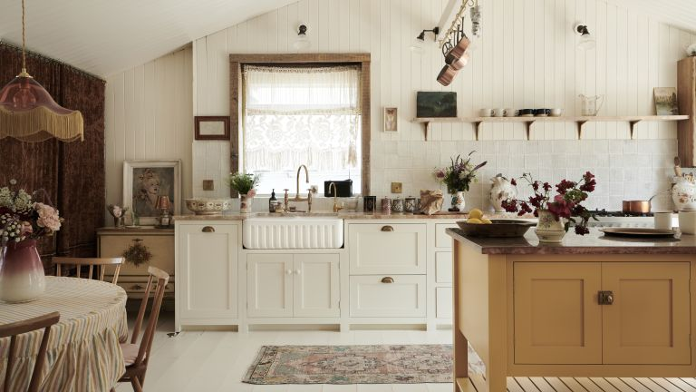 A white kitchen with off-white shaker cabinets, shiplap walls and white textured backsplash tiles