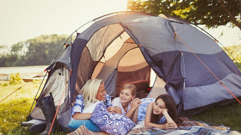 Camping with kids: a woman camps in a meadow with her two young daughters