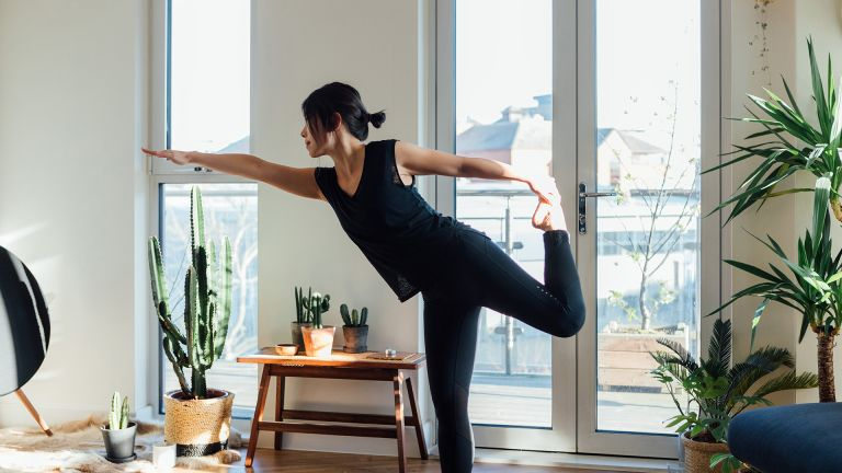 woman doing yoga in apartment surrounded by plants