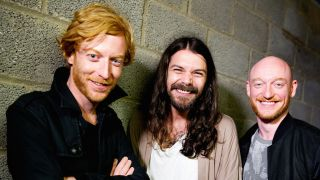 Biffy Clyro smiling in front of a breezeblock wall