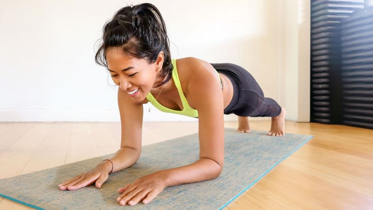 Woman wearing exercise kit learning how to do a plank