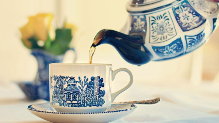 tea being poured from tea pot into cup