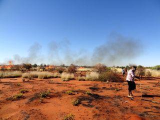 aboriginal hunters in an Australian desert cooking sand monitor lizards.