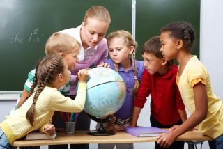 Kids gather together to look at a globe with their teacher.