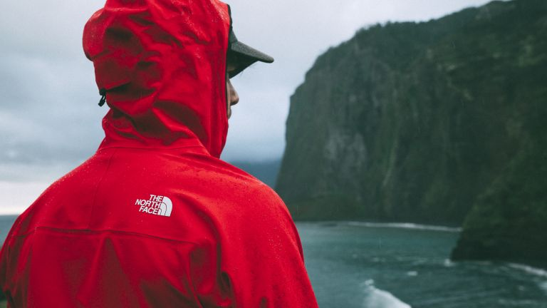19 best waterproof jackets 2019: a man wears The North Face Apex jacket in red while staring out at the sea in the rain