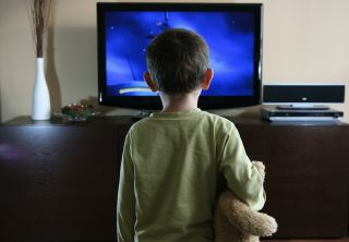 A kid watches television.