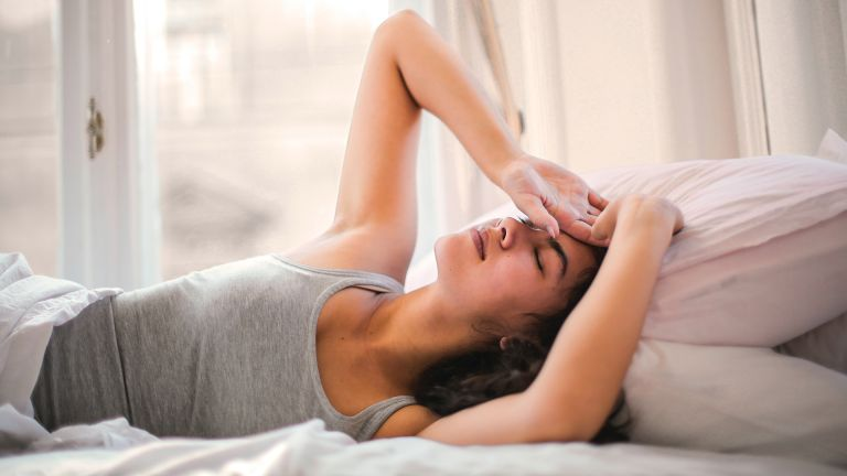 best mattress for back pain: woman in bed looking uncomfortable