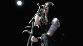 Satyr of Satyricon singing into a mic and holding the mic stand