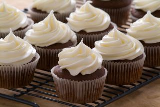 Chocolate cupcakes with cream cheese frosting sit on a baking rack.
