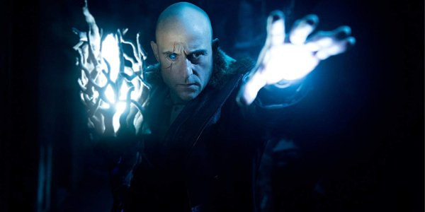 Shazam! Mark Strong stands menacingly in the cave with his glowing hand and staff