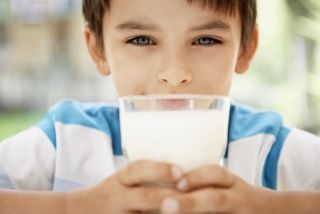 a boy drinking a big glass of milk