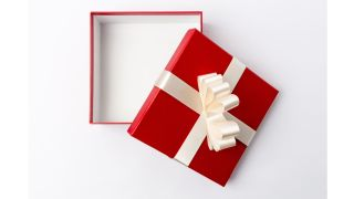 An open empty gift box wrapped in shiny red paper and wide white ribbon