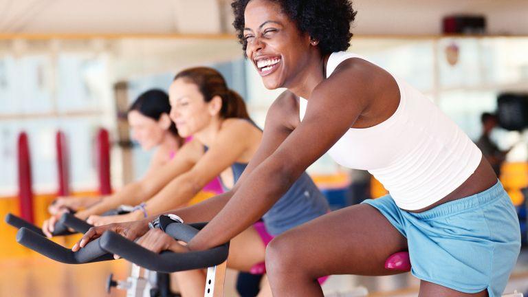 Women in the gym on stationary bikes enjoying the exercise bike benefits