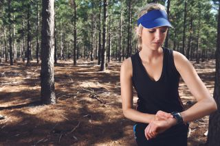 A woman checks her fitness watch while walking in the woods.
