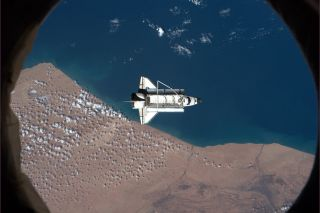 Space shuttle Discovery floats over southern Morocco during the ISS fly-around before departing to return to Earth.