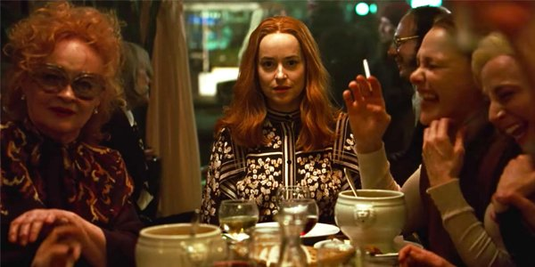 Dakota Johnson Suspiria at a table with drinks and witches