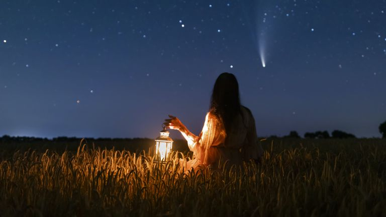 Woman in field with lantern on background of Comet Neowise C/2020 F3 - stock photo
