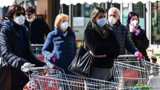 Residents wearing face masks wait outside a store in Codogno, southeast of Milan, Italy, on March 11, 2020, just a day after Italy imposed unprecedented national restrictions on its 60 million residents to help slow the spread of COVID-19.