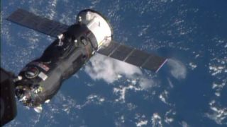An unmanned robotic vehicle docks to the International Space Station above the blue Atlantic Ocean.