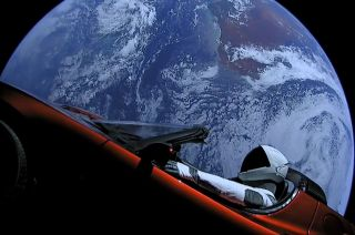SpaceX's Starman mannequin sits inside Elon Musk's red Tesla Roadster with Earth in the background, shortly after the initial launch of SpaceX's Falcon Heavy rocket on Feb. 6, 2018.